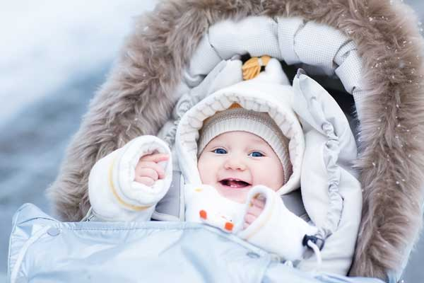 baby bundled up in stroller taking a walk in the winter