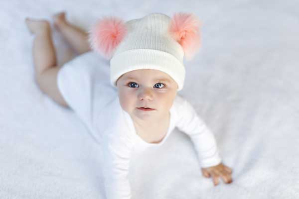 little baby with snow hat and pom poms