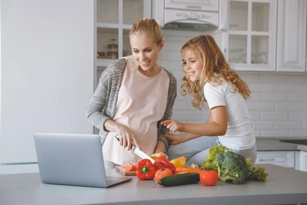 pregnant mom cutting vegetables on counter with daughter