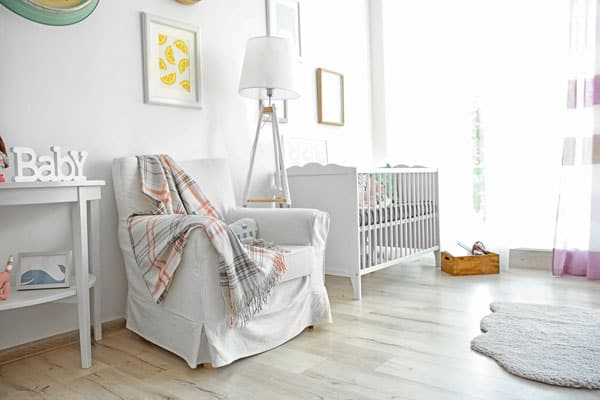 modern white nursery set up for newborn including a breastfeeding station with chair