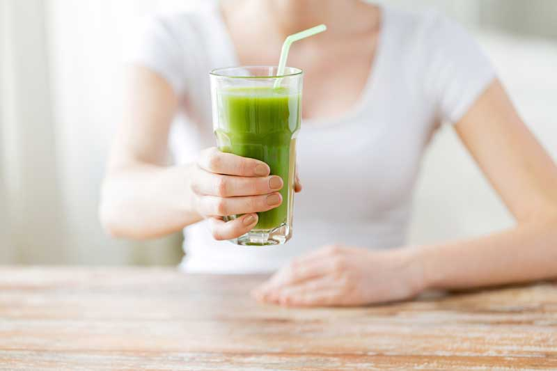 woman holding green smoothie with lactation supplements