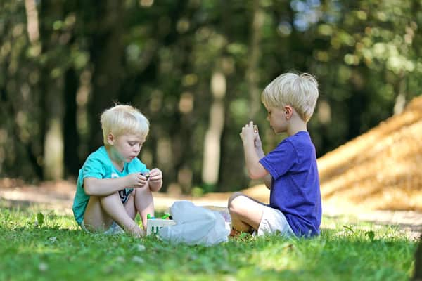 two blonde boys playing outside in grass